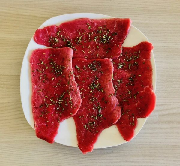Season the meat with salt and black pepper to taste. Finely chop the rosemary leaves and sprinkle on top.