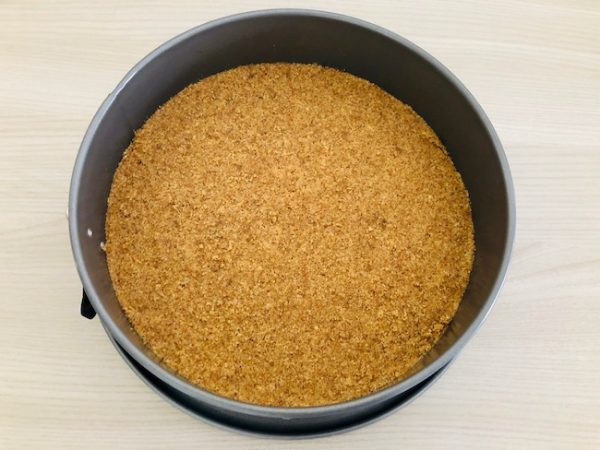 Line the bottom of a cake pan (diameter 22 cm) with parchment paper. Transfer the mixture, pressing it to form an even layer. Leave it in a refrigerator for 30 minutes.
